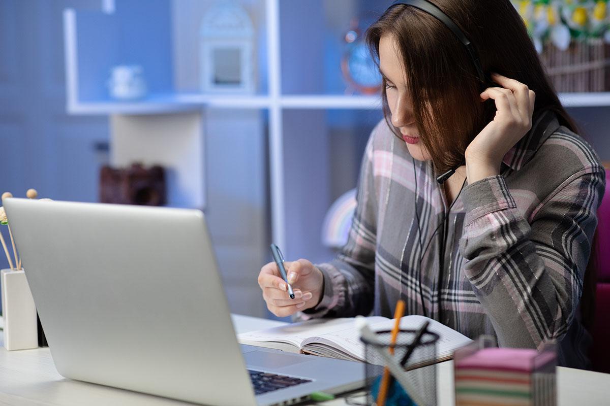 Girl student wear headphones study online with internet teacher